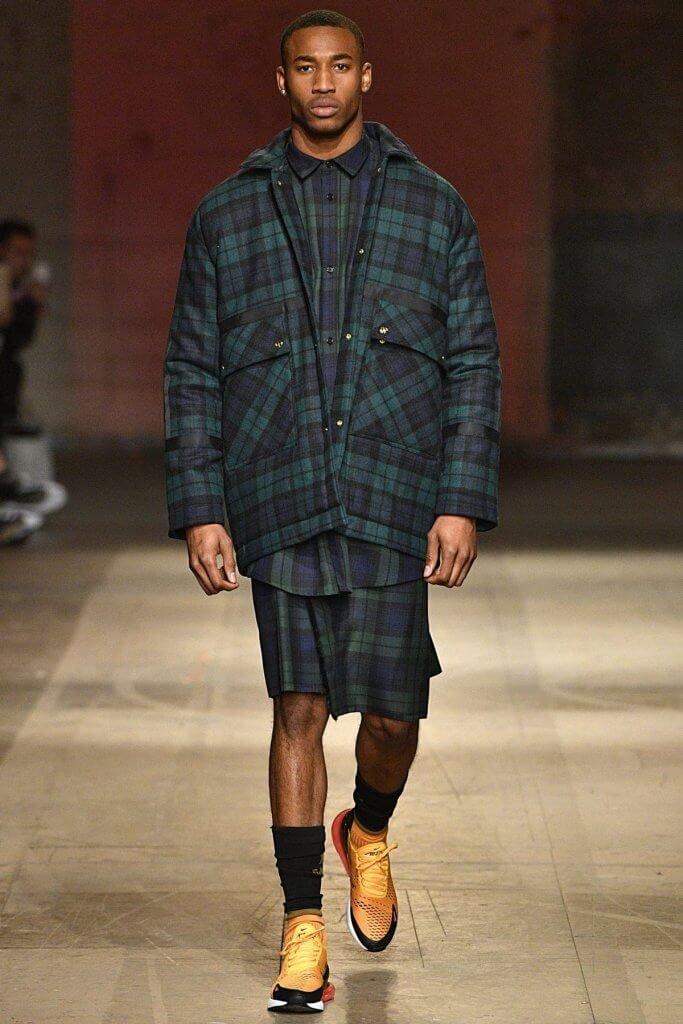 Model wearing a matching tartan print outfit of a shirt, jacket, and kilt.