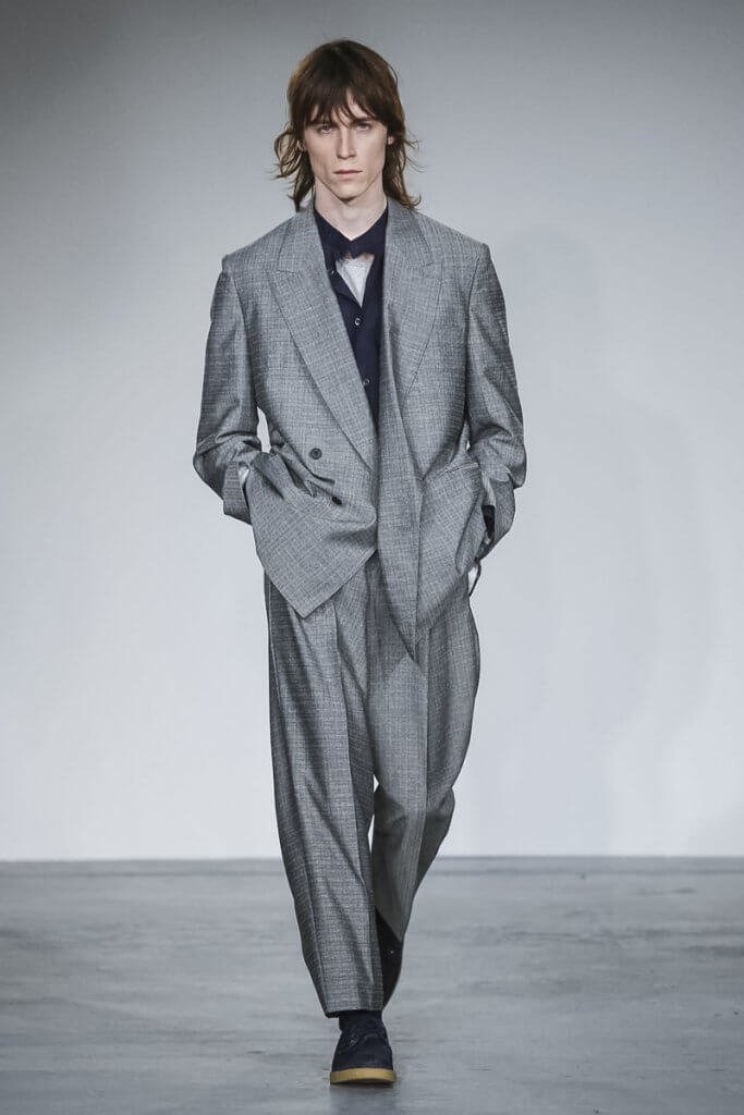 Model wearing a loose fitting silver suit on the catwalk.