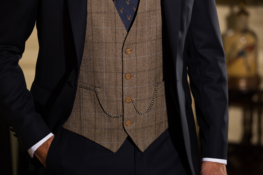 Close up shot of a light brown checked waistcoat against a dark suit jacket and trousers.