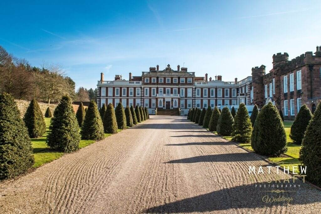 A landscape shot of Knowsley Hall taken from the viewpoint of the path lined by bushes.