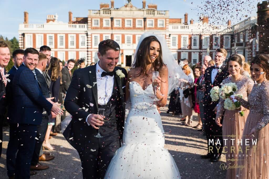 The bride and groom walk together arm in arm with guests throwing confetti over them.