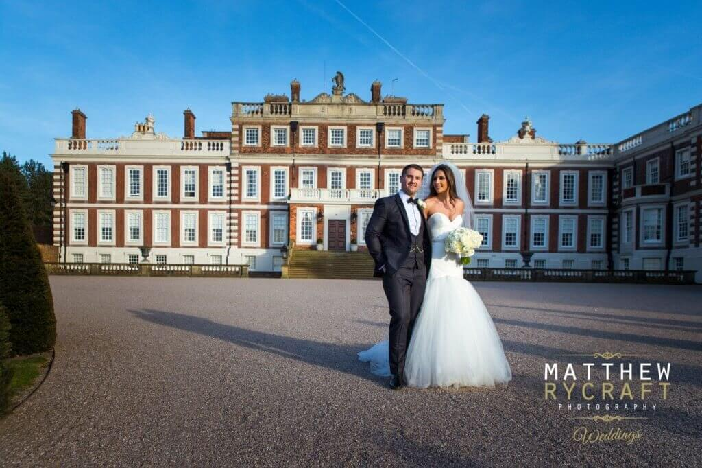 The bride and groom walk arm in arm in front of Knowsley Hall.