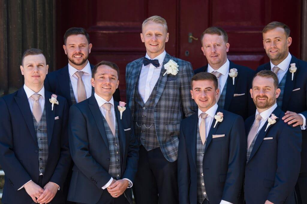 The groom and his groomsmen pose together, with the groom wearing a patterned suit jacket.