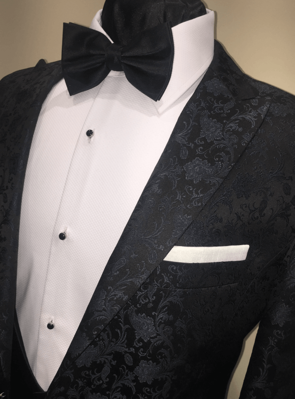 Close up shot to show the detailed texture of a black dinner suit jacket.