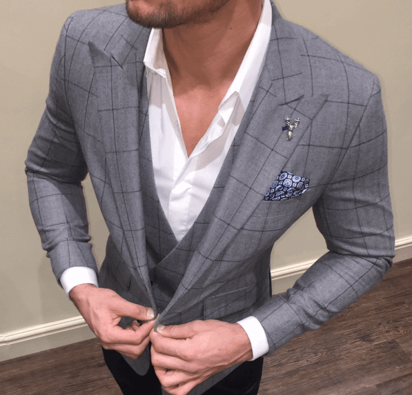 High angled shot of a man buttoning the waistcoat of his light grey suit.