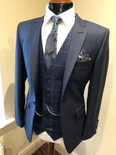 Dark navy suit jacket on a mannequin with waistcoat, tie and pocket square in mixed patterns.