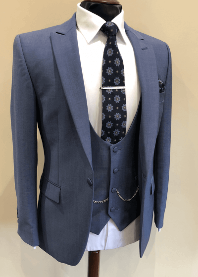 Blue grey suit jacket and waistcoat on a mannequin with a patterned tie.