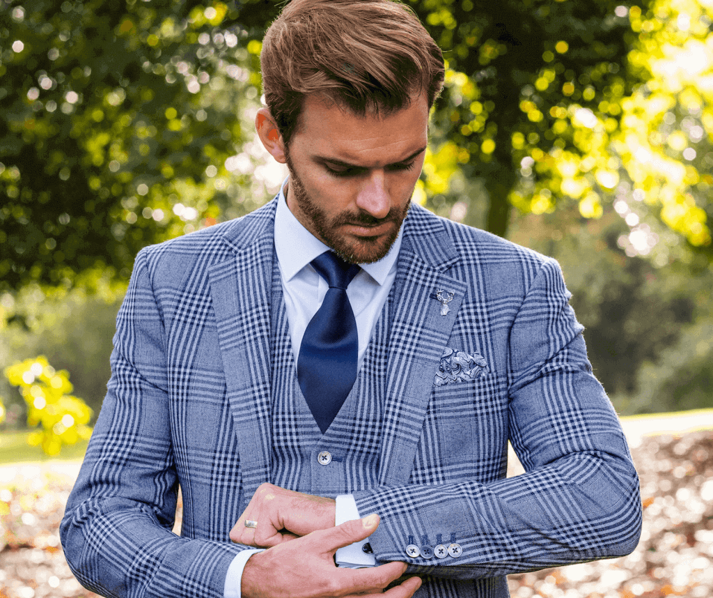 A model fixes the cuff on his checked suit jacket.
