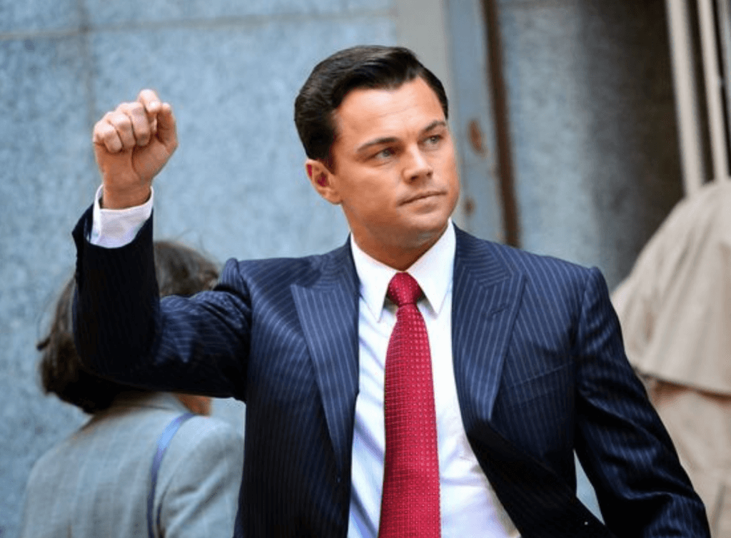 Leonardo DeCaprio wearing a striped navy suit and red tie in The Wolf of Wall Street.