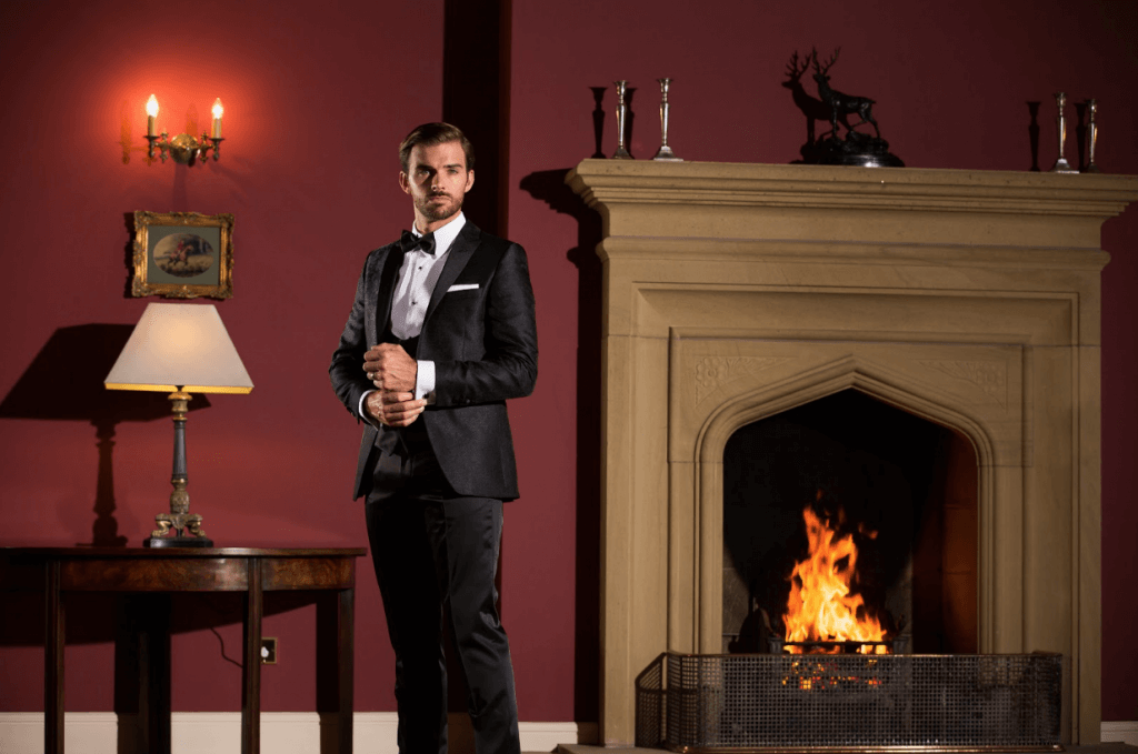 Model stands by a fireplace wearing a tuxedo and fixing the cuff on his suit jacket.