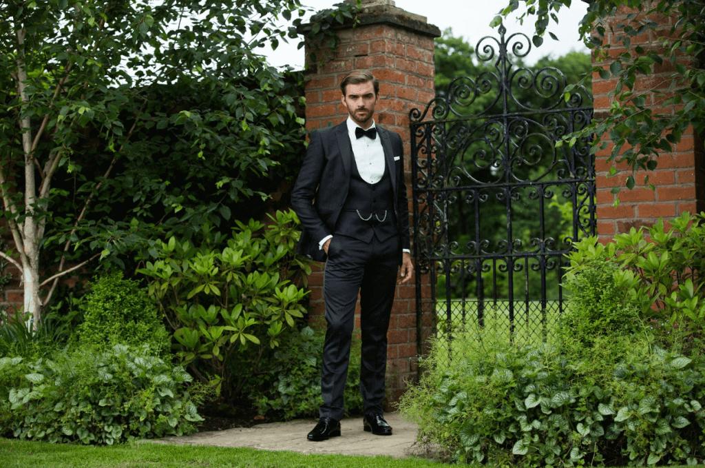 Model wears a tuxedo in a garden, stood by a gate.