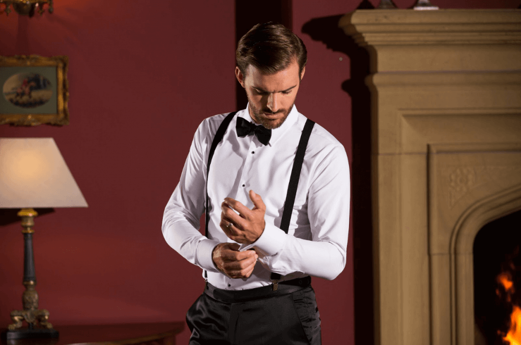Model fixes the cuff on his white shirt, whilst wearing braces and a bow tie.