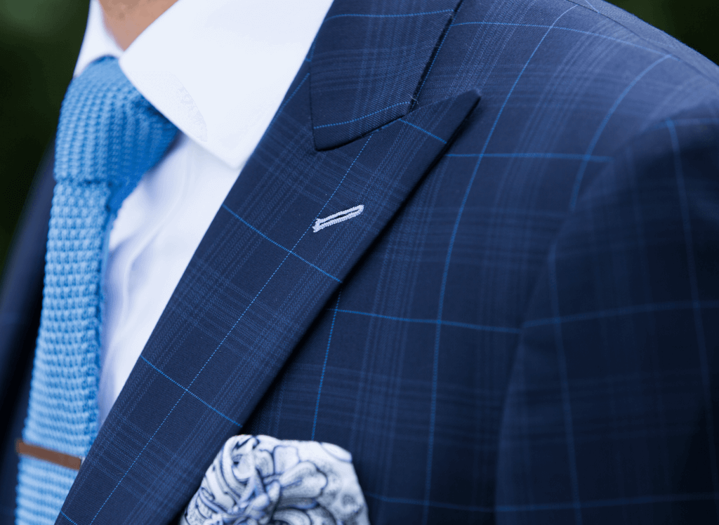 Close up shot of a patterned navy suit jacket with a mixed pattern tie and pocket square.