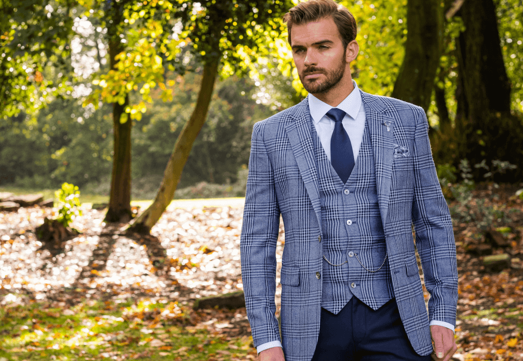 Model looks off camera and wears a 3 piece suit with a matching checked suit jacket and waistcoat with dark trousers.