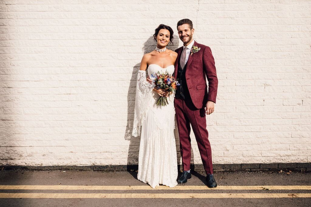 A happy bride and groom pose in front of a brick wall, with the groom wearing a maroon suit.