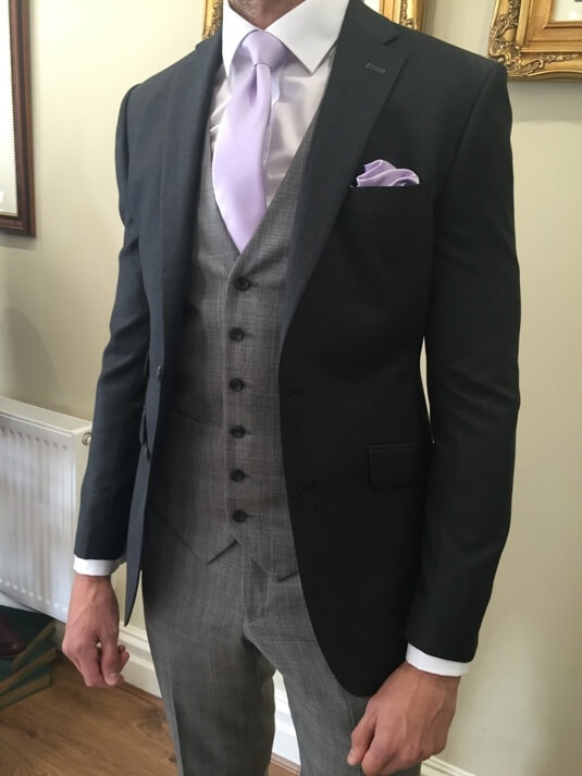 A mix and match suit consisting of a grey waistcoat and trousers, black suit jacket and lilac tie and pocket square.