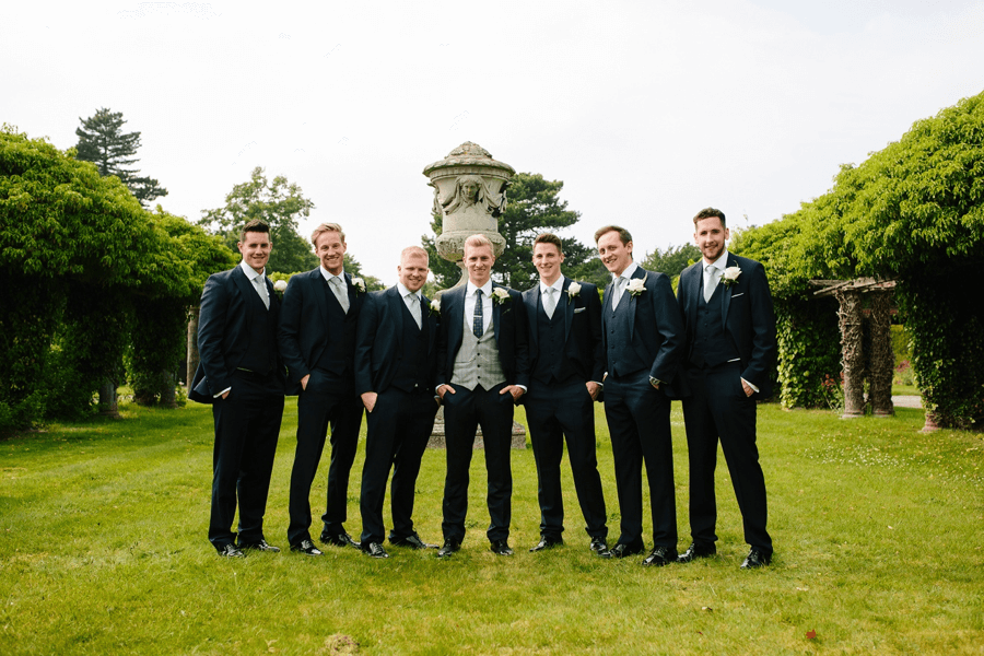 Groom and his groomsmen pose together in a garden, with the groom wearing a different waistcoat to everyone else.