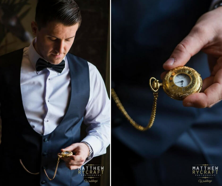 Detail shot of the groom holding a golden pocket watch which is attached to his waistcoat by a chain.