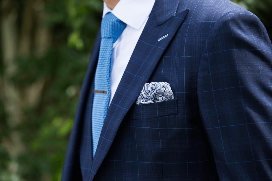 Close up shot of a patterned pocket square against a patterned dark navy suit jacket.