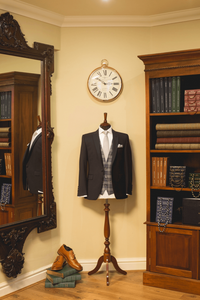 Shot of a patterned waistcoat on a mannequin with a dark suit jacket over the top next to a bookcase and mirror.