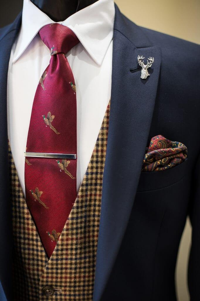 Close up shot of a navy suit jacket with a checked waistcoat and red patterned tie and pocket square.