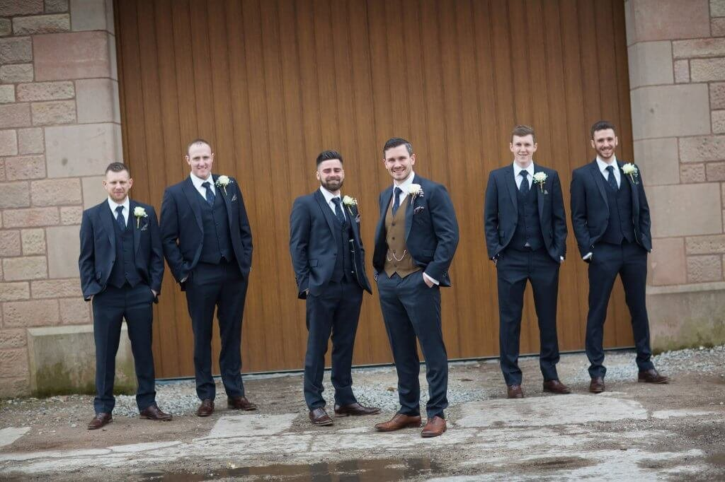 The groom and his groomsmen pose together in front of the wedding venue. The groom's suit differs slightly to everyone else, as he is wearing a different coloured waistcoat.