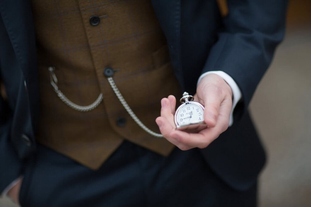 The groom holds a pocket watch in the palm of his hand, which is attached to his waistcoat on a chain.