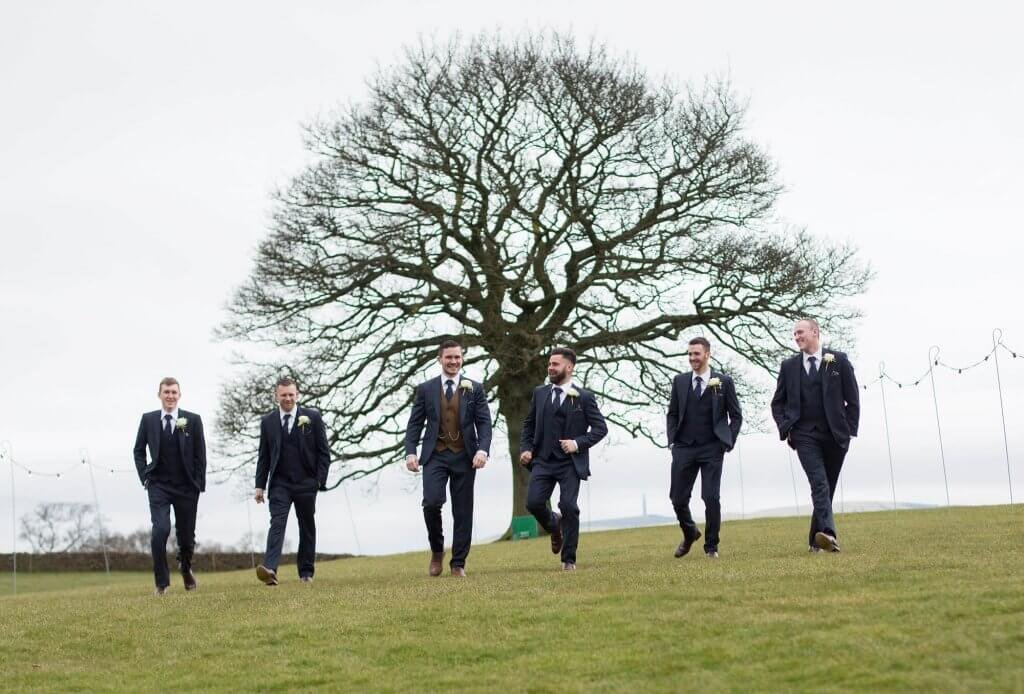 The groom and his groomsmen walk together in front of a large tree.