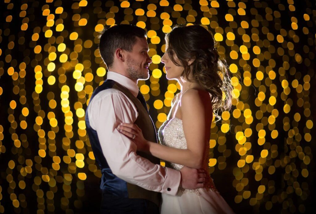 A side on shot of the bride and groom holding each other against a low lit background.