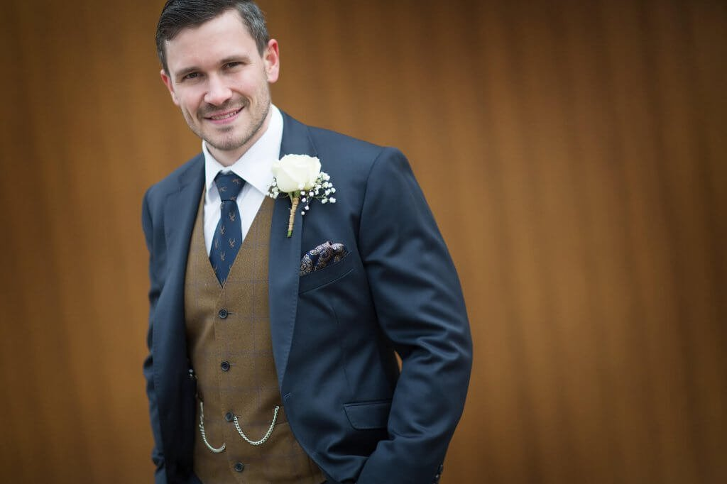 Close up of the groom wearing a mixed 3 piece suit. The waistcoat is brown against a dark suit jacket.
