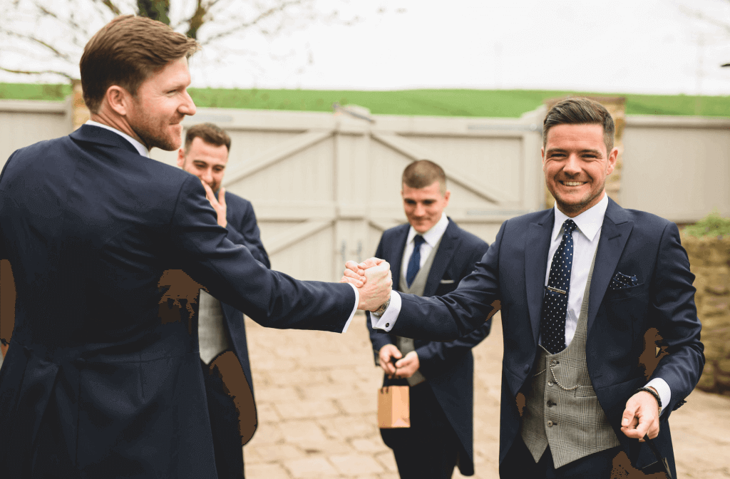 Candid shot of the groom shaking hands with one of his ushers. The groom wears a 3 piece dark navy suit with a grey waistcoat.