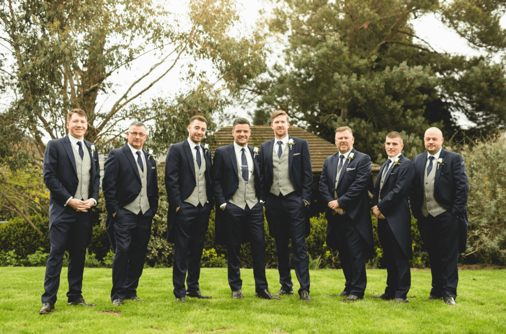 The groom and the groomsmen pose in the gardens of the venue. They are all wearing a 3 piece dark navy suit with a contrasting grey waistcoat.