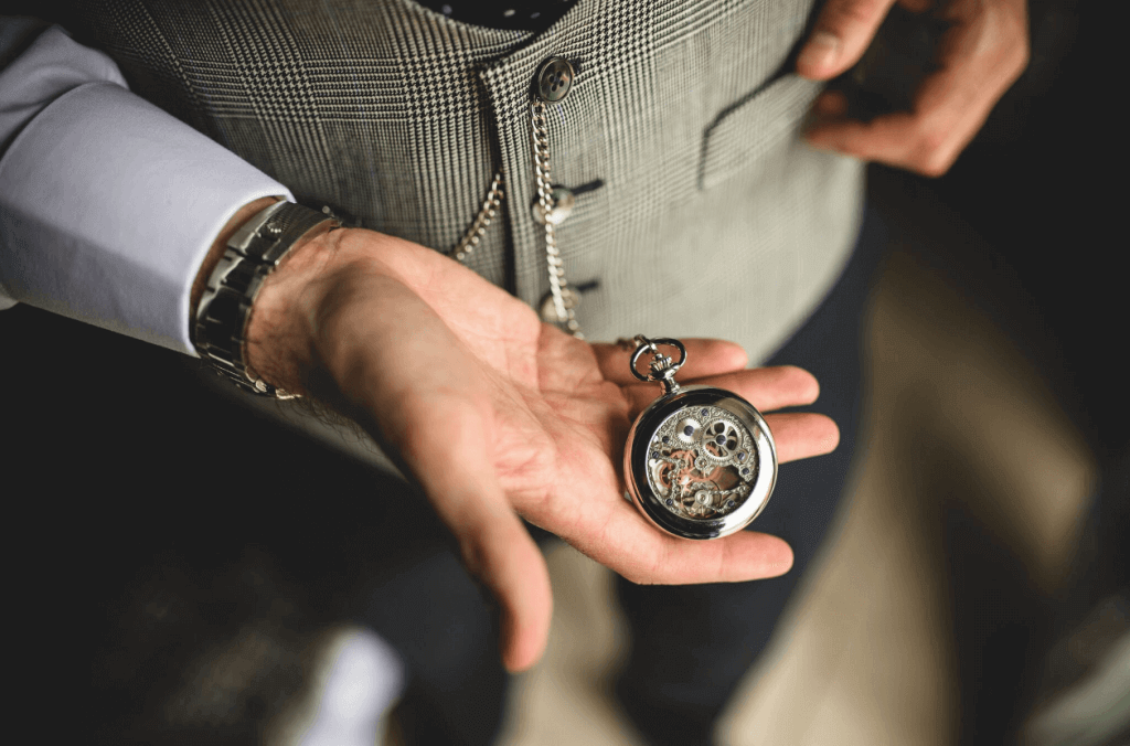 Detail shot of the groom holding a pocket watch attached to his waistcoat on a chain.