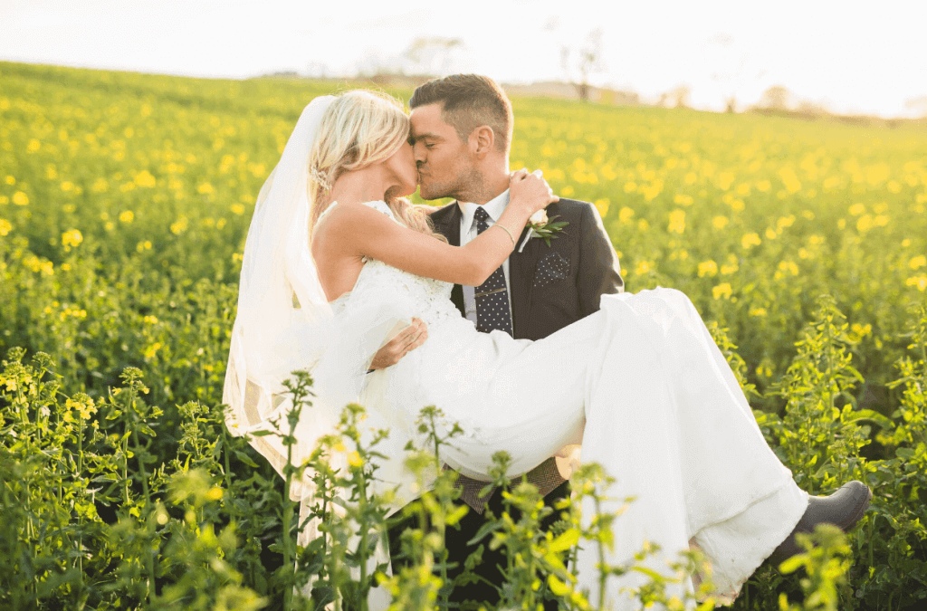 The bride and groom share a kiss in a field, with the groom holding the bride.