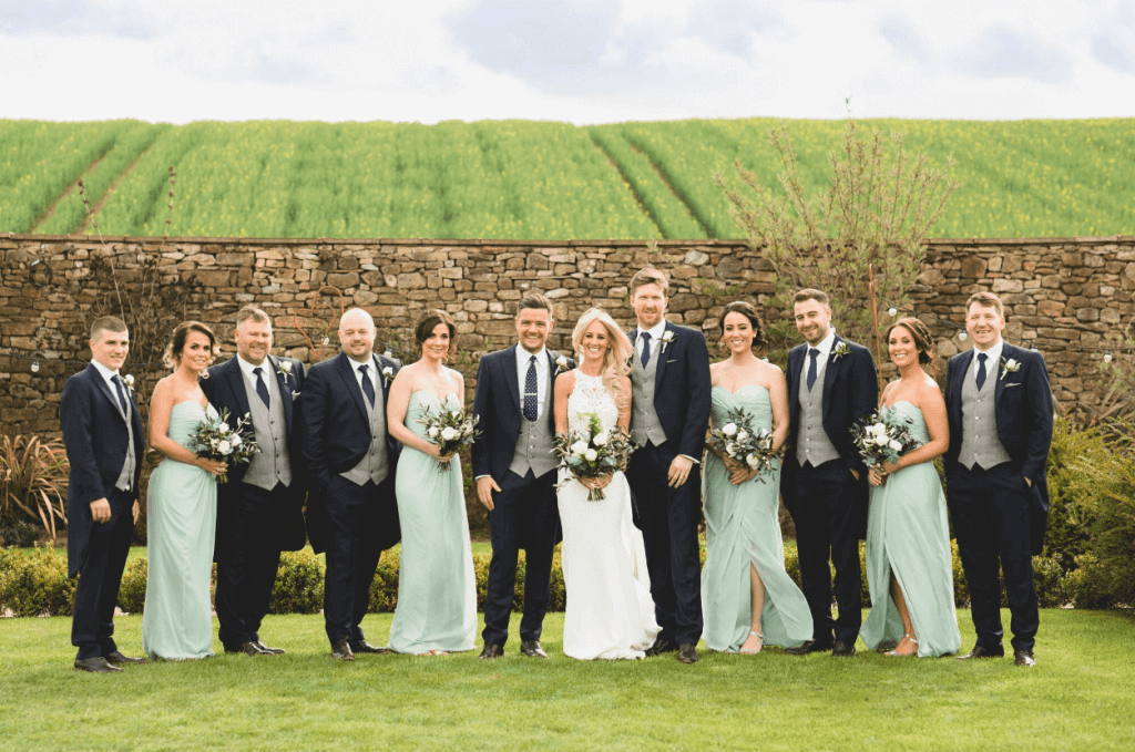 The bridal party pose for the camera in front of a stone wall and field. The groomsmen all wear a 3 piece suit with a grey waistcoat, with the bridesmaids wearing mint dresses.