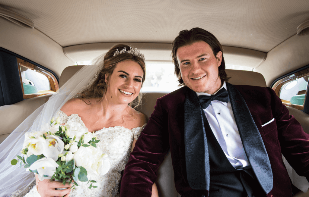 The bride and groom smile at the camera in their wedding car. The groom wears a burgundy velvet suit with a bow tie.