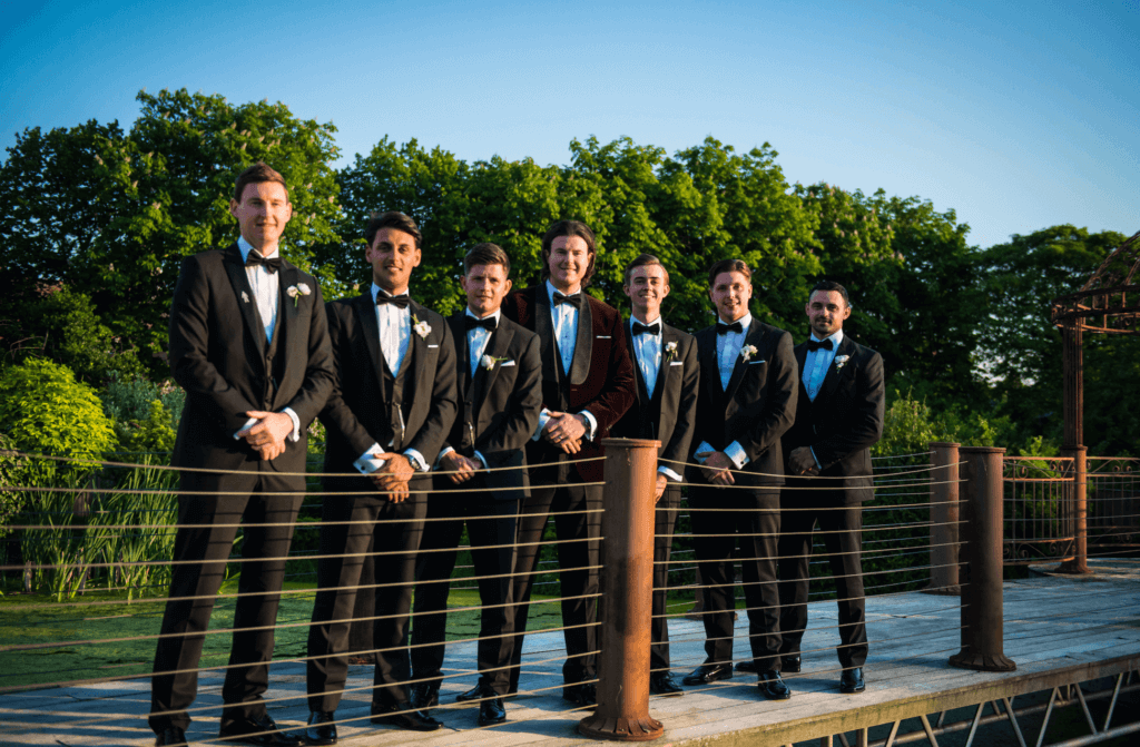 The groom and his ushers pose for the camera. The groom wears a burgundy velvet suit and the ushers are wearing black suits with bow ties.