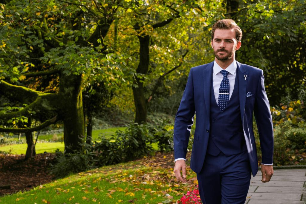 Model walks through gardens wearing a 3 piece navy suit.