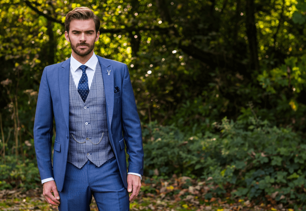 Model in the woods looking at the camera wearing a 3 piece blue suit. His waistcoat is a checked grey/blue mix.