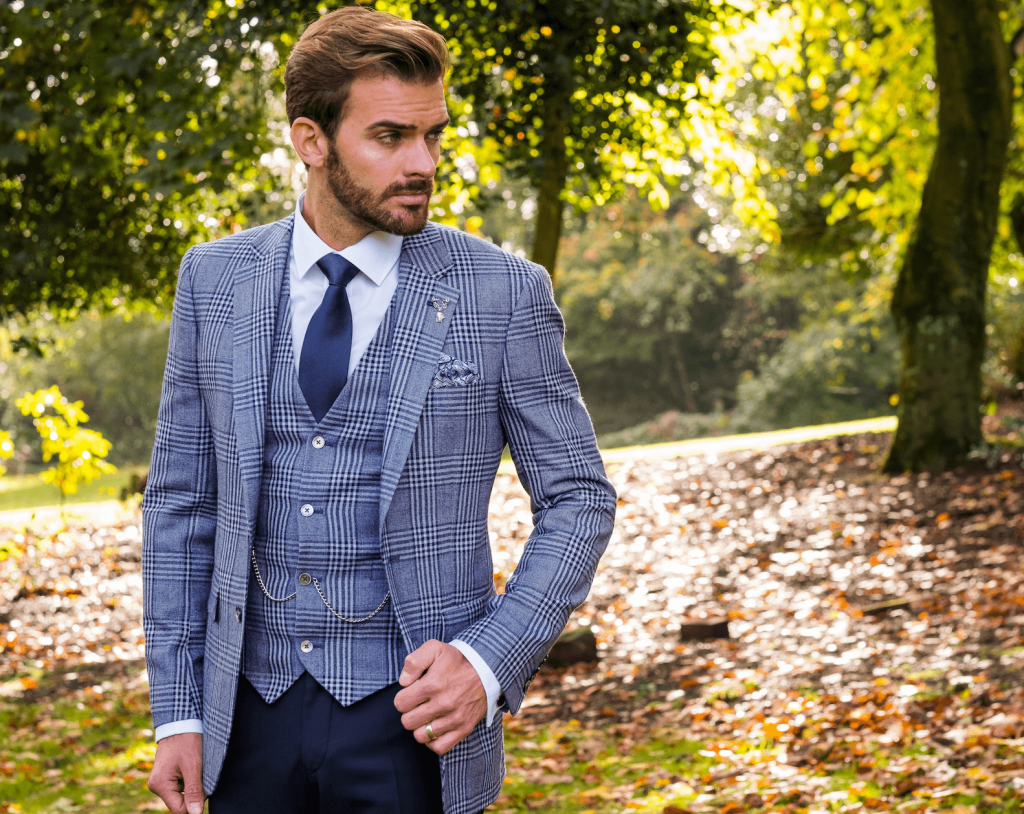 Model poses in a checked 3 piece blue/grey suit.