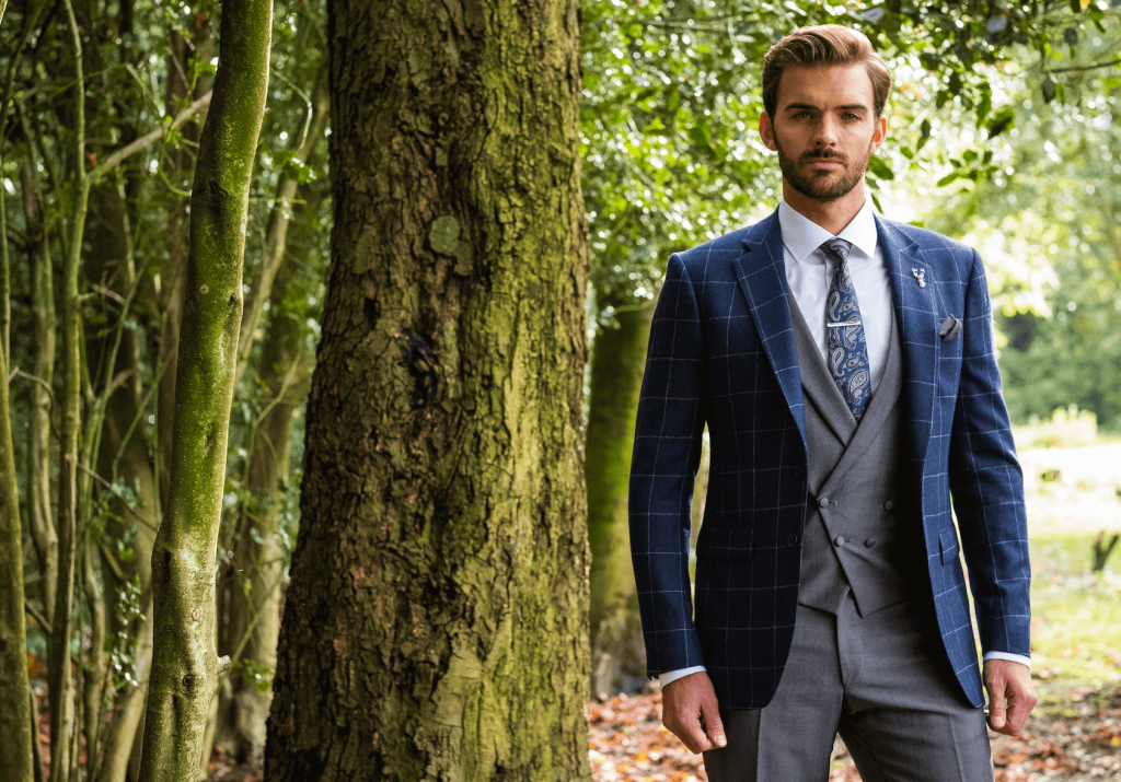 Model in the woods wearing a blue checked suit jacket with a grey waistcoat and grey trousers.