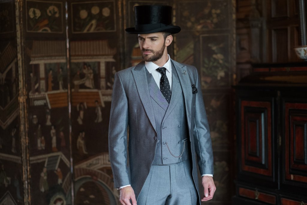Model wears a 3 piece silver suit with a black top hat.