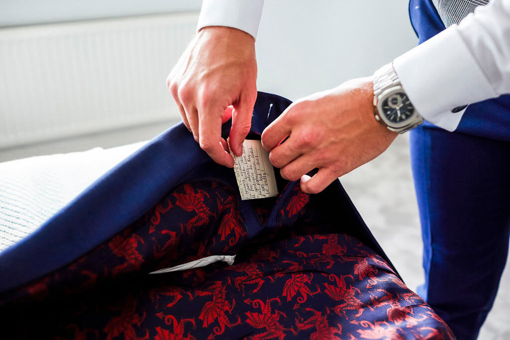 A close up shot of a handwritten note being placed into the inner pocket of a navy suit jacket. The lining of the suit jacket consists of a red and blue pattern.