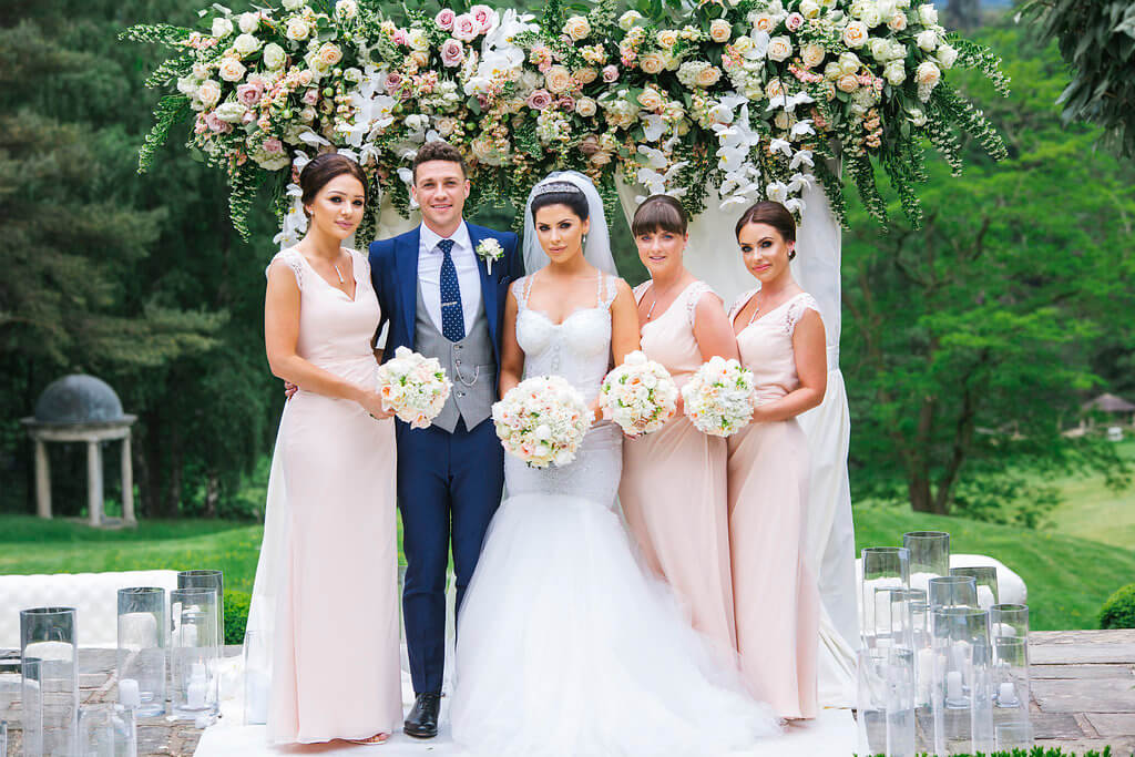 The bride and groom pose with the bridesmaids in front of their flower arch.