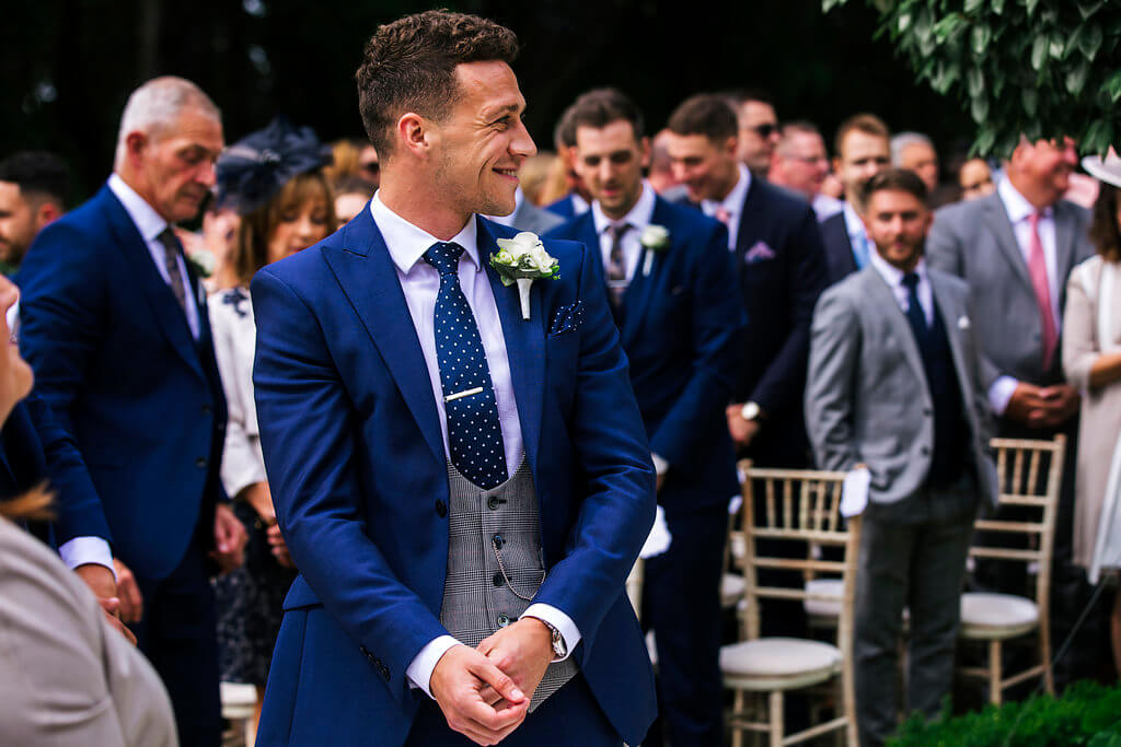 A candid shot of the groom smiling as he waits for his bride. The groom is wearing a 3 piece navy suit with a grey checked waistcoat.