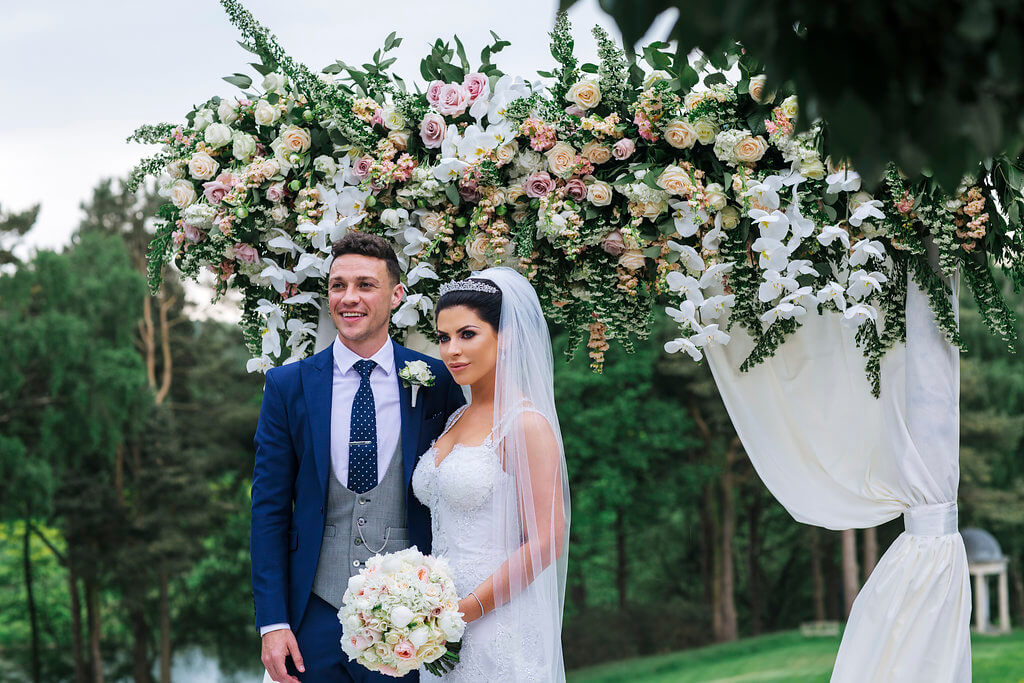 The bride and groom standing by an arch of flowers. The groom is wearing a navy suit with a grey waistcoat, with the bride holding her bridal bouquet.