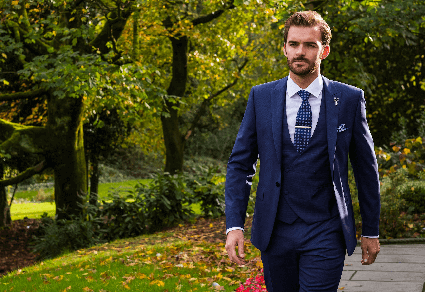Man walking through gardens wearing a dark navy 3 piece suit with a spotted navy tie.