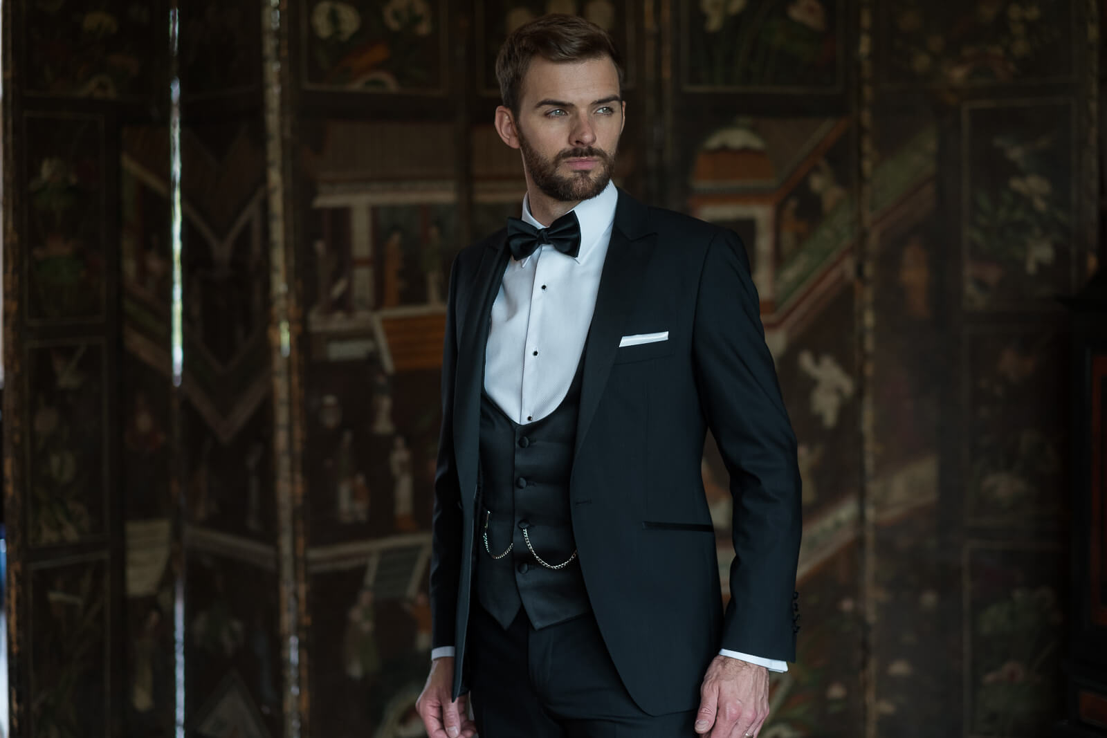 Model looking slightly off camera wearing a 3 piece black suit with a bow tie.