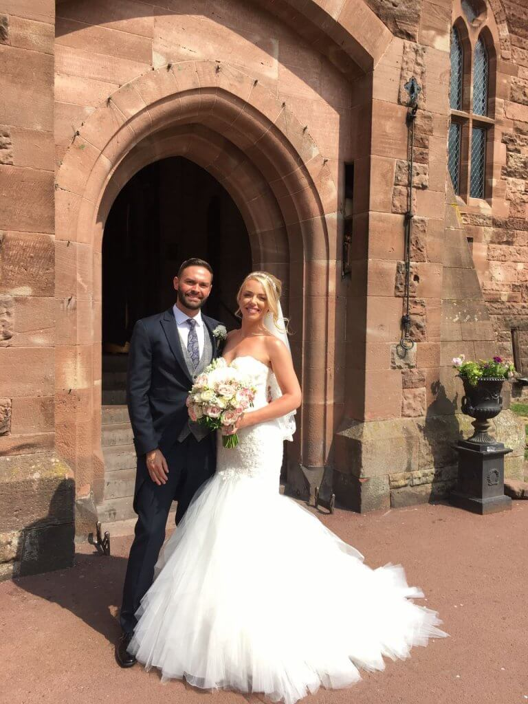 Bride and groom smiling at the camera stood outside of Peckforton Castle. Bride is holding a bridal bouquet.