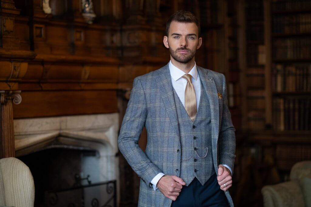 Gent wearing a grey check jacket & waistcoat with navy trousers